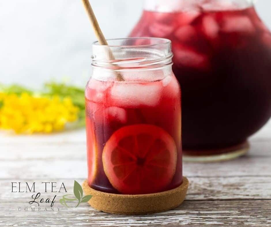 Mason Jar of Hibiscus Tea with a pitcher next to it.