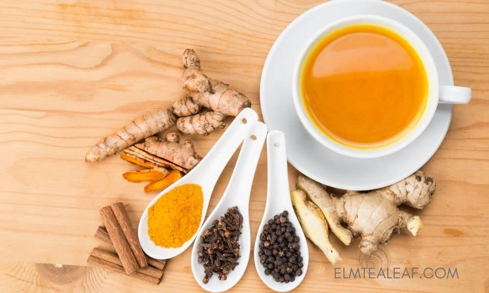 Cup of Turmeric Tea with ginger, clove and peppercorns on the table