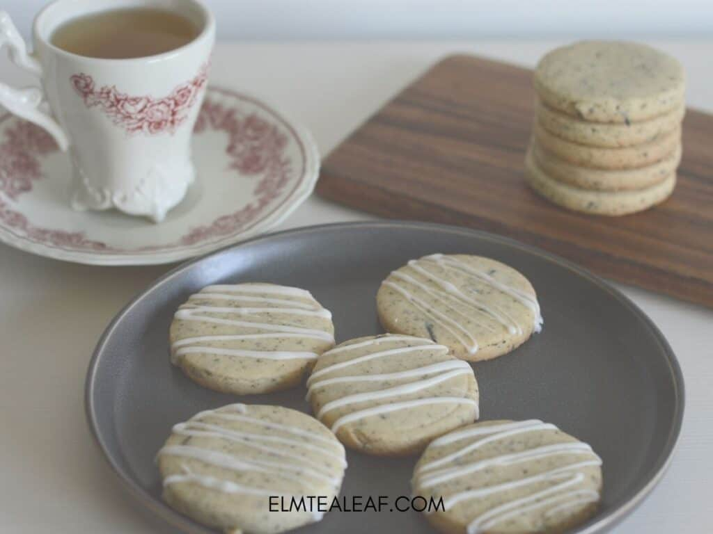 Plate of Earl Grey cookies with teacup of tea and stack of cookies in the back.